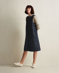 Workwear dress in a medium-weight, supple, indigo-dyed denim. Boat-ish neck. Corozo shank buttons at either side. Topstitched seams. Two large stitched-through patch pockets. Single patch pocket at back.