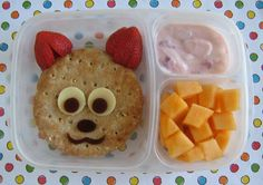 bento box lunch: strawberry yogurt, cantaloupe and a ham and cheese sandwich on a multigrain round, topped with a fox face made with strawberry ears, white cheddar eyes and blueberry fruit leather for the nose, mouth and pupils.