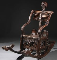 A Russian Style Macabre Carved Wood Skeleton Form Rocking Chair. Highly carved in the form of a grotesque skeleton raised on a four legged wood base with carved facial masks and extending rockers terminating in carved lions heads and claw feet.