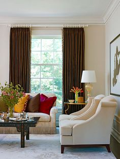 Love the chocolate curtains against the white walls, and the colorful pillows on sophisticated furnishings! {via BHG Four Ways to Define Your Signature Style}
