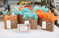 """For an Around the World themed party: The hostess spray painted cereal boxes and made small suitcases out of them, filling them with glider airplanes and other fun goodies. These suitcases were placed in """"Baggage Claim"""". """""""