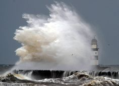 Troubled waters: The harbour lighthouse at Seaham, County Durham, is engulfed as towering waves explode against the sea wall this morning, driven by gale force winds off the North Sea as a storm sweeps across Britain