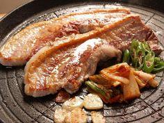 삼겹살 Pork belly. Koreans fry this on a stone grill with garlic slices, mushrooms, and my favorite is 김치 (kimchi). You then wrap the pork slices with lettuce and perilla leaves and top it with the other grilled vegetables and 삼장.