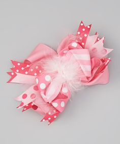 With a sweet marabou feather puff in the center and a bundle of classically printed ribbons, this adorable bow will top outfits off with a charmingly dainty touch.