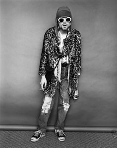 """Kurt Cobain reveled in black humour and self-deprecation of his sudden celebrity. This heroin addict """"costume"""" was complete with a seven day beard, half-on women's clothes & sunglasses, a cigarette and a bottle."""