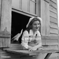 Getty Stock Photo : Acadian Dress. A young woman dressed in traditional Acadian clothing leaning out of a window at the Longfellow-Evangeline Memorial Park.