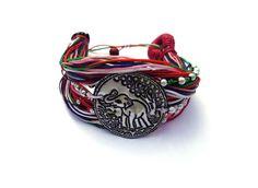 Brede armband gemaakt van verschillende dunne draadjes rood, wit, rose, bruin, blauw, groen (multicolour) waxkoord. Gedecoreerd met kraaltjes met in het midden een dun metalen schildje met een afbeelding van een olifant. Lengte inclusief sluiting 23 cm. Breedte 4 cm. Hele aparte armband! Zie afbeelding.