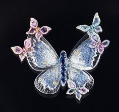 AN EXQUISITE COLOURED DIAMOND, ROCK CRYSTAL AND MOTHER-OF-PEARL CLIP BROOCH, BY WALLACE CHAN – Photo c/o Christie's    Designed as a butterfly, the body set with marquise, pear and heart shaped diamonds, to the butterfly specimen wings encased in carved rock crystal with mother-of-pearl back, enhanced by brilliant-cut colourless to yellow diamond trim and accents, mounted in titanium,6.3 x 6 cm  Signed Wallace for Wallace Chan