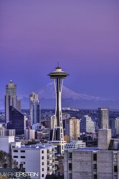The Seattle Space Needle projects into the Seattle skyline as the sunsets on Mount Rainier.