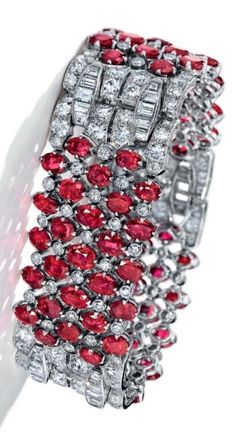 VAN CLEEF & ARPELS - AN ART DECO RUBY AND DIAMOND BRACELET, CIRCA 1935. Designed as a three flexible panels set with oval and cushion-cut rubies and old-cut diamonds, joined by old and baguette-cut diamond links, with French assay mark for platinum, signed Van Cleef & Arpels, numbered.
