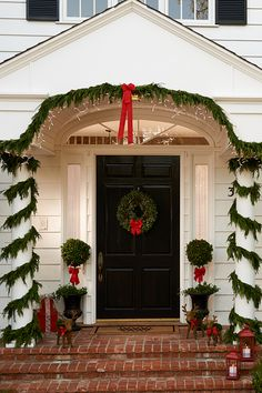 Dress your porch for the holidays! Wrap your outdoor pillars in fresh garland and set out red lanterns for whimsical décor.
