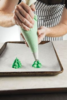 "MERINGUE christmas trees cookie -Add green food coloring to meringue - Put green meringue in a piping bag fitted with a "" star tip. Start with a 1 ½""-wide star, then pipe two more stars on top of the first, each ½"" smaller than the last, to form a three-tiered Christmas tree. Repeat steps to make additional trees."