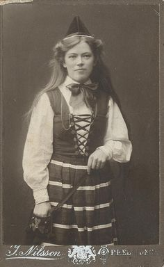 This woman was photographed in Örkelljunga, in the southern most part of Sweden (Skåne) in a regional costume - but the dress is actually a Rättviksdräkt (Rättviksdress) that comes from Rättvik, Dalarna, a completely different part of the country. At the time it was high fashion for girls to go to the photographer and there borrow a suitable costume and then be portrayed in it, which is probably the case here.