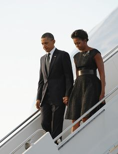 Michelle arrives at John F. Kennedy International Airport in New York City wearing a black belted dress.