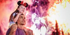 A little girl wearing Mickey ears sits on her father's shoulders and looks up at fireworks