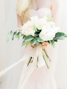 A beautiful bouquet is supposed to complement the bride's style, not overwhelm it. So if the bride is planning a modern and minimalist look, keep the flowers simple, too. A cool idea is to limit yourself to only one or two types of flowers, and then complete the bouquet with dark greenery.