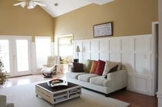 Southern Revivals  -- i love the panels behind the couch.. its just wood (2x4's, maybe?).. all painted white