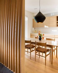 The dining area is separated from the entrance with a custom wrap-around screen that provides privacy without closing the space off completely. The slats are made of CNC'ed wood.