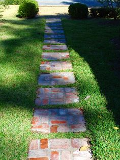 Repurposed Bricks. Antique brick steppingstones bisect this lawn. The classic herringbone pattern is set in a series of squares that reinforces the strong geometric design.