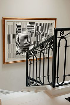 Jorge Elias. Love the pattern play: railing, picture, stairs -- and gold/black contrast.