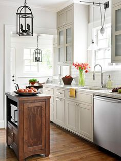 A lantern-style fixture hung above this kitchen's tiny island provides adequate lighting for the dainty work space. The dark color accentuates the grain of the wooden island and flooring. A pair of differently shaped pendants above the sink illuminate that area and lend a splash of contrast.