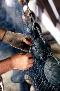 Richard Doublerly knitting a fishing net by hand. (1988) | Florida Memory