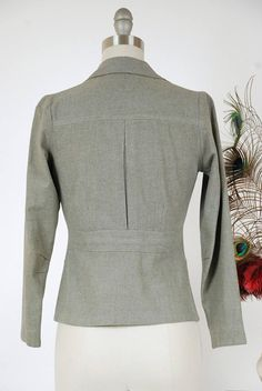 Vintage 1930s belt back jacket is a rare find - these jackets are a scarcity in menswear and are truly a unique find in the world of womens fashion. This fabulously tailored jacket offers single breasted, peaked lapels and a dual button closure. The pockets are pleated down the center. The back features a center vent style action back and fitted, high waist belt back. The sleeves are darted at the This jacket would look fabulous with Hepburn pants or a crisp skirt. This garment closes with…