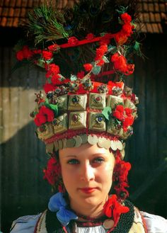Bride from Transylvania  |  The traditional headdress of Transylvania is covered all around w/ little metal plates, each adorned w/ a precious stone. The lower end is trimmed w/ a string of coins (gold, silver or copper, depending on one's wealth) & the upper part of the headdress is filled (like a flower pot) w/ peacock feathers or artificial flowers  |  5 January 2014  //   Transylvania is a historical region in the central part of Romania. Bound on the E. & S. by its natural borders, the…