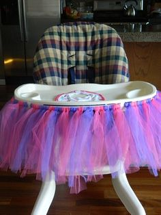 I decorated the high chair with a pink and purple tutu.