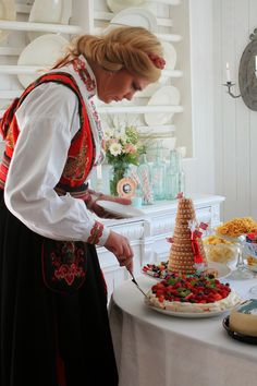 Norwegian celebration! This is soo NORSK! Large cake table , You can se the kransekake (tower, made of almonds), bløtekake (layerd cream cake with berries on top). The girl is wearing a bunad from Telemark.