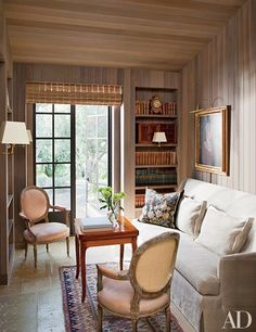 Antique French fauteuils and an 18th-century games table are gathered in the red-cedar-paneled library at Casa Kulanu, the Napa Valley home that designer Rela Gleason shares with her husband, Don. The heirloom portrait over the sofa has been attributed to John James Audubon.