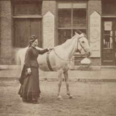 A serious faced young woman and her lovely horse walk down the street during the 1880s.