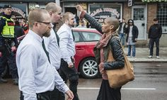 Swedish woman's defiant gesture in front of fascist march in Sweden. Bravery in action.