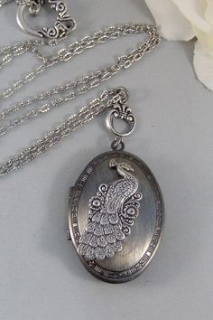 This silver locket is very retro, and beautiful. A lovely antiqued silver peacock locket.    The outside of the locket has a slight decoration