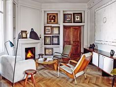 The living room is stocked with a Royère armchair, a Prouvé coffee table, and a Perriand sideboard.