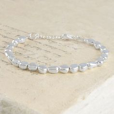 This solid sterling silver bracelet features smooth silver nuggets that move beautifully against the wrist. Classic and simplistic with beautiful organic forms and textures. #Otisjaxon #Jewellery #Accessories #Bracelet #Bangle #Women