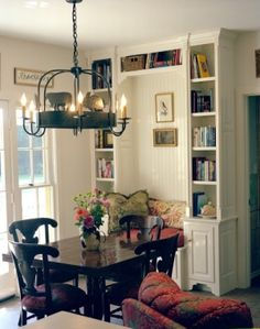 Love this nook, with the beadboard backing and bookshelves behind the dining table and chairs. by lois