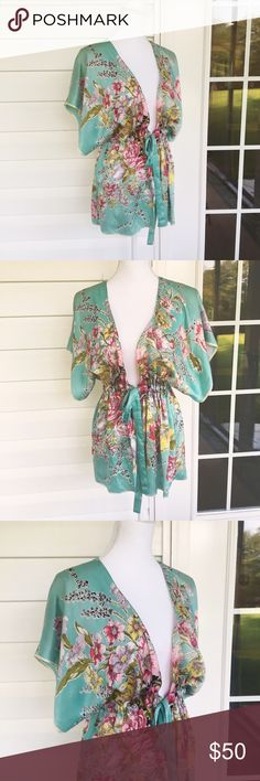 CAbi Floral Silk Wrap Made from 100% silk, this charming wrap will be a bright spot in your wardrobe. The bright blue is covered in a variety of pink and yellow flowers. The tied waist is flattering. In good condition. 10610 CAbi Tops Camisoles