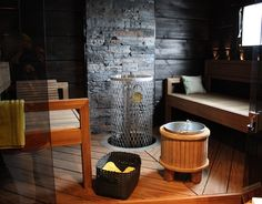 "Modern Finnish Sauna: Traditional benches can be replaced in the sauna with benches that provide a nice change from your sauna room. In addition, they are very practical thanks to mobility. Thus benches can easily be washed from time to time. Vesikiulu has been around a wooden ""barrel"" and improve coal dark wall heater at gray stone brick. Comfortable and stylish."