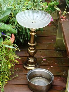An old brass lamp and ceiling light shade - repurposed as a bird bath