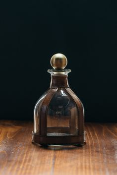 This equestrian leather decanter was designed to celebrate the unity of the horse (the glass) and the rider (the leather). This simple, yet elegant Equestrian Distressed Leather Glass Decanter features a metal stopper and round glass overlaid with distressed brown leather and copper rivets.