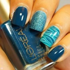 Greyish teal color nails with a marble design. Super cute nail art.