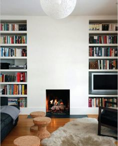 Pop out the fireplace and tile with large grey tiles. Have bookshelves built to fit into surrounding fire.