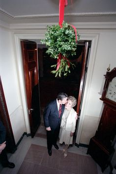 President Ronald Reagan and Nancy Reagan kissing under the mistletoe while viewing White House Christmas decorations. 12/9/84.