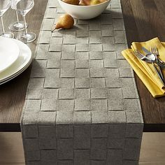 Handwoven in a basketweave pattern, strips of grey felt fashion a table runner with lots of chunky, modern appeal. Due to their handcrafted nature, table runners may vary slightly in pattern and size.