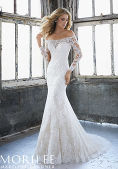 Morilee | Madeline Gardner, Karlee Style 8207 | Elegant Fit and Flare Wedding Dress Featuring an Off the Shoulder Illusion Neckline and Crystallized Venice Lace Appliqués on Net. Long Illusion Sleeves and a Zipped Back Closure Trimmed in Covered Buttons Completes the Look. Available in Three Lengths: 55″, 58″, 61″. Colors Available: White, Ivory, Ivory/Crème
