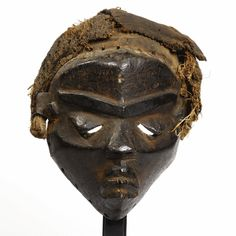 A Superb Pende Mask, Democratic Republic of the Congo mbuya, of hollowed oval form, the pointed chin beneath the small frowning mouth, the small pyramidal nose bisecting the pierced heavy lidded eyes beneath the V-shaped unibrow, with fiber headdress attached; exceptionally fine deep dark brown patina with traces of red pigment. height 11 1/4 in. 28.6 cm