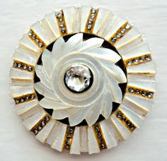 Mother of pearl button. Base border has a ray motif with alternating rows of tiny cut steels or paste. Over that, a metal disk and a mother of pearl, carved pinwheel shape. In the center, a clear paste stone.