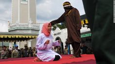 A young woman is caned in public on December 28 for violating Sharia law in Banda Aceh, Indonesia.