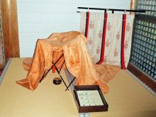 A museum display of a standing curtain with a heian robe draped over an incense perfumer.